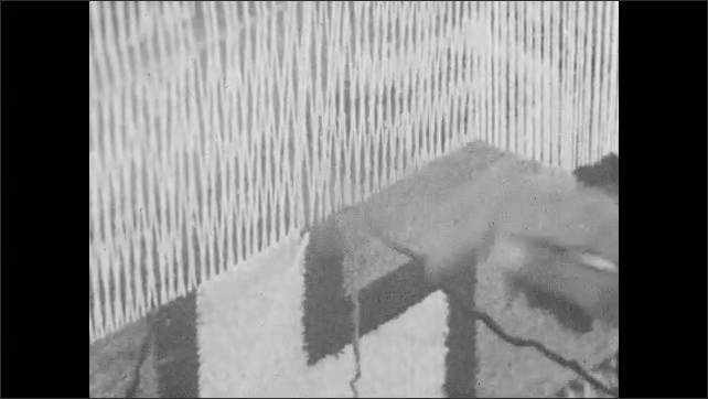 1930s: Woman kneels at outdoor loom and weaves Navajo blanket. Blanket on loom/