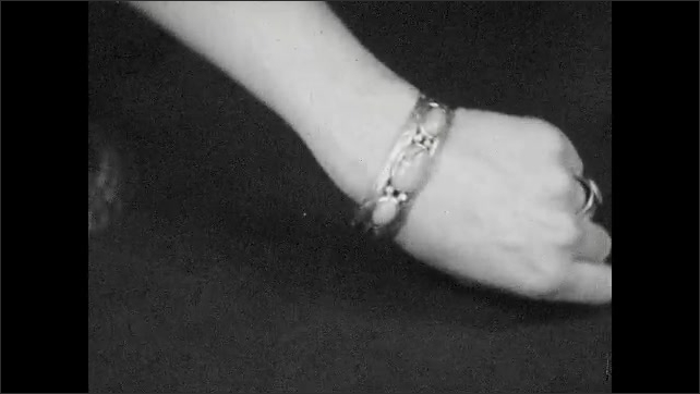 1930s: Woman's arm shows off hammered silver bracelet and ring inlaid with stones. Woman picks up elaborate silver Navajo necklace.