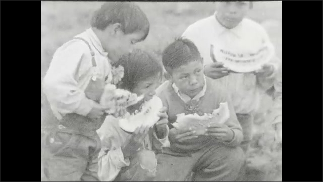 1930s: A man cuts a watermelon in half on the ground, children sit around and they watch him. Four children eat watermelon slices. Children and a man eat watermelon slices.