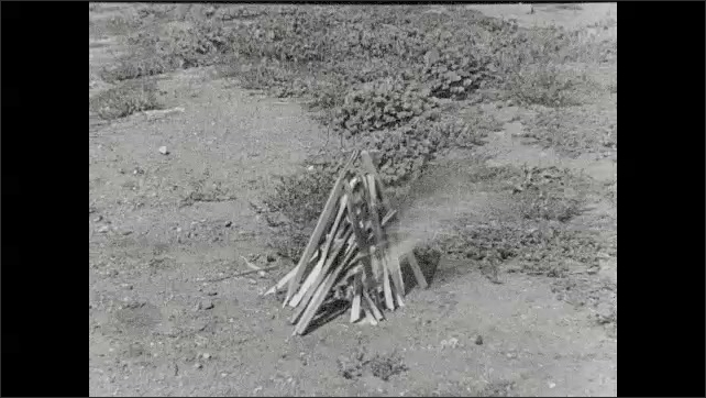 1930s: A young man puts a piece of hay that burns under sticks that quickly start to burn. Pile of sticks burn on the ground. A boy does lasso rope tricks.
