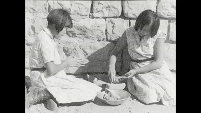 1930s: Intertitle. Two girls sit on the ground and make pottery with clay.