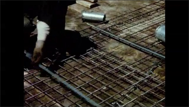 1970s: UNITED STATES: steel rods in concrete. Man cuts metal grid. Man nails down mesh.