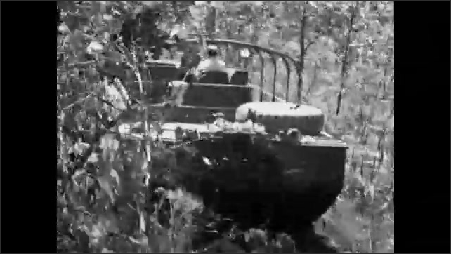 1960s: Amphibious craft pushes through trees and shrubs on land near water.