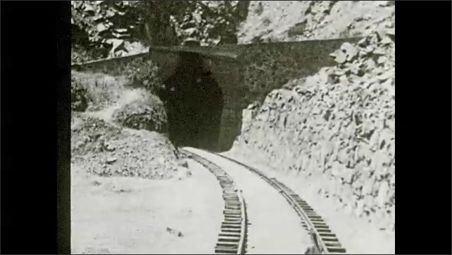 """1930s: Mountain.  Train moves down tracks and through tunnels.  Text reads """"Many tunnels have been blasted through the highest peaks and ridges."""""""