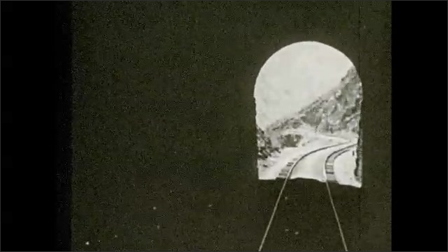 1930s: Mountains.  Train moves down tracks and through tunnels.  Text describes the Rimac River.