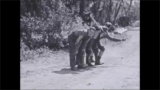 1930s: Dog stand on rock in woods. Text placard. Dog runs and jumps over four stooped men. Text placard. Dog and trainer walk toward stream.