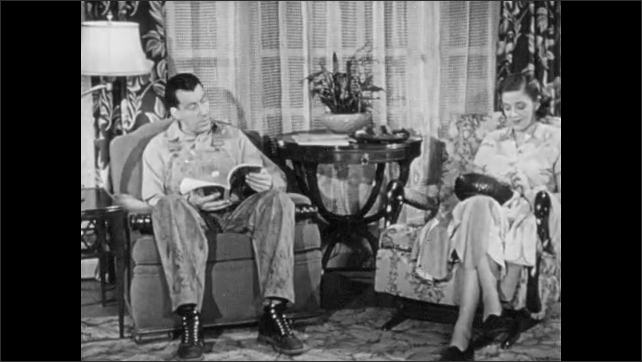 1960s: Man and woman sit and talk in living room.