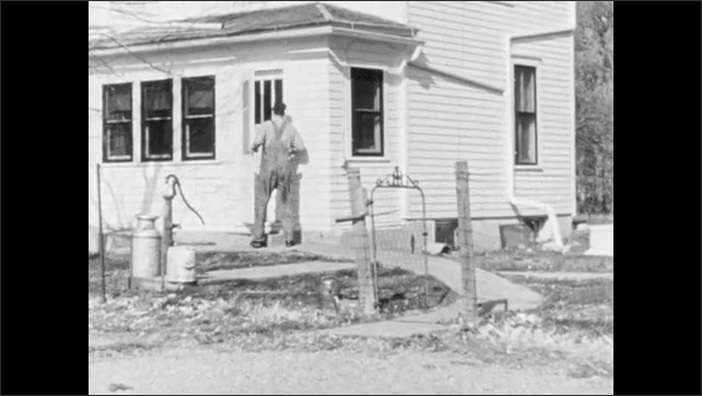 1960s: Farmer walks out of barn and runs into house.  Woman dusts table.  Man and woman talk.  Man hands corn to woman.