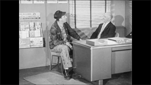 1960s: Men speak.  Man gestures to chair.  Men sit.  Man opens binder.