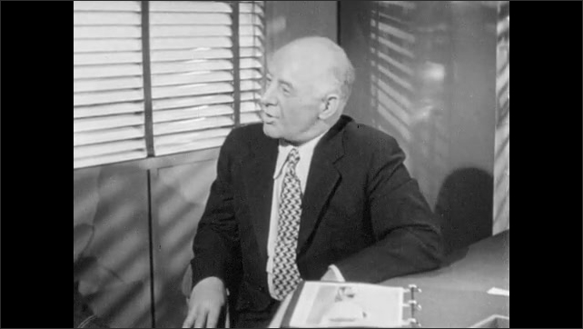 1960s: UNITED STATES: men talk in office. Farmer talks to man in suit. Man sits at office desk.