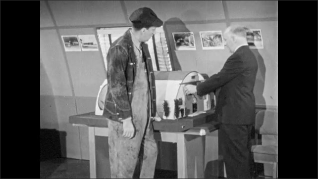 1960s: UNITED STATES: farmer talks to man in office. Model of building in office. Farm building model.