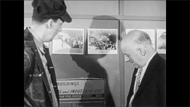 1960s: UNITED STATES: clock on wall. Man sits at desk in office. Men talk in office. Man gives photos to farmer. Men shake hands. Man waves goodbye