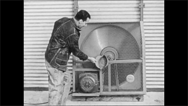 1960s: UNITED STATES: man switches on drier in tunnel. Man sticks hat on cage
