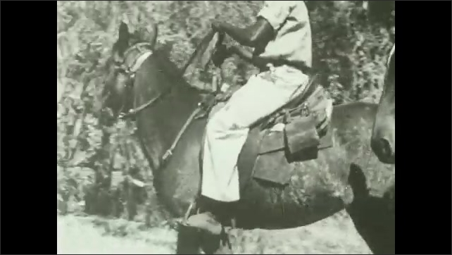 1930s: Man gets off horse and points at ground.  Men ride off.  Horse stands near trees.