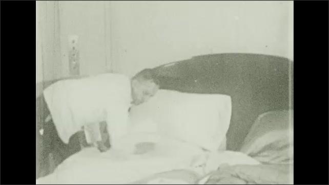 Bermuda 1930s: Intertitle card. Man makes bed. Ocean.
