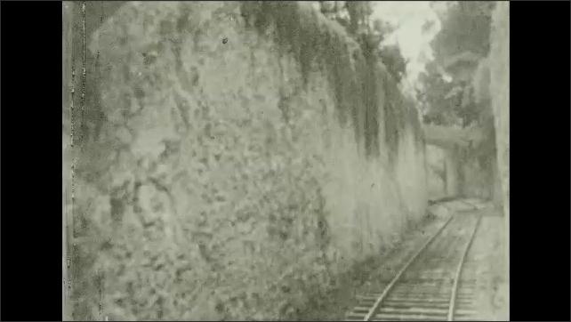 Bermuda 1930s: Train travels through tunnel. Sign for beach. Women on beach.