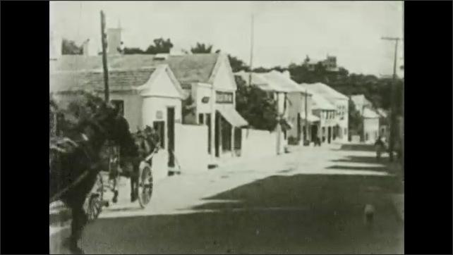 Bermuda 1930s: Intertitle card. Horse drawn carriage travels down street. Church.