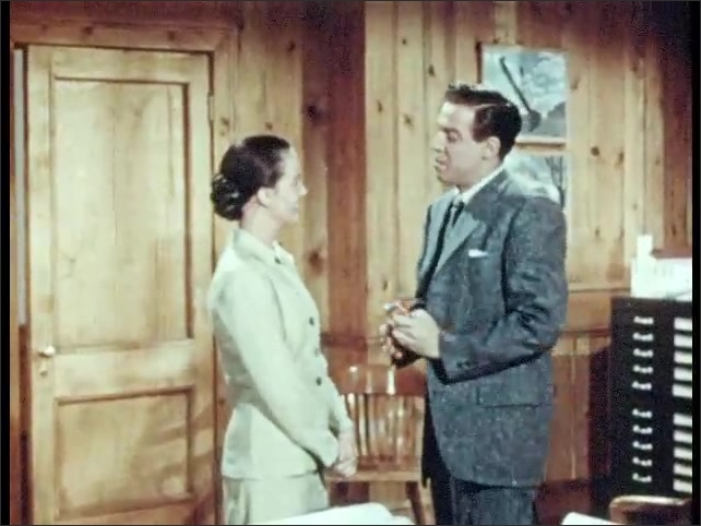 1950s: Man stands up from desk, talks to woman, picks up suit jacket from chair back, puts on jacket, smiles.