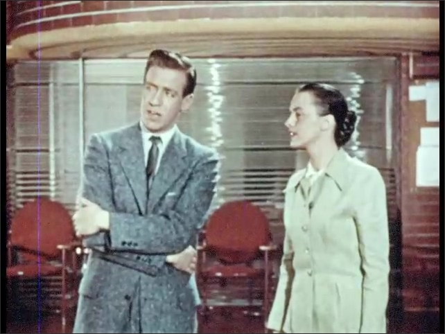 1950s: Man and woman stand in lobby of building, look around. Man talks to woman, woman nods, looks around.