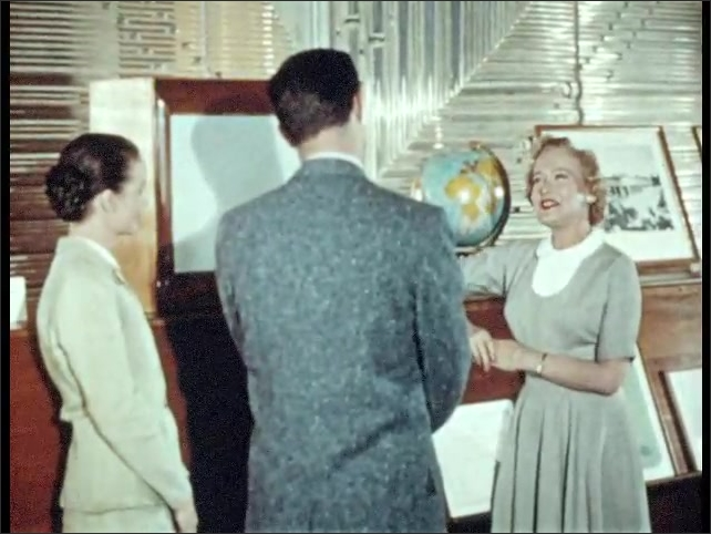 1950s: Person displays various drawings of Egyptian architecture and decorations. Woman talks to man and woman in presentation room, escorts them to another display room.