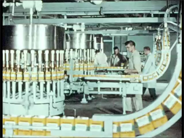 1950s: Man sits at machine, adjusts lever, looks into pot. Wax pours onto metal spatula. Packages travel through assembly machines in factory.