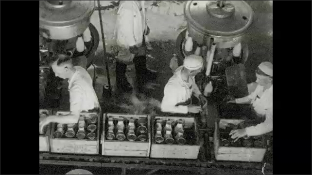 1930s: UNITED STATES: workers at factory supervise milk bottles on machine. Lady watches bottles. Carts collect milk. Men load milk bottles into crates.