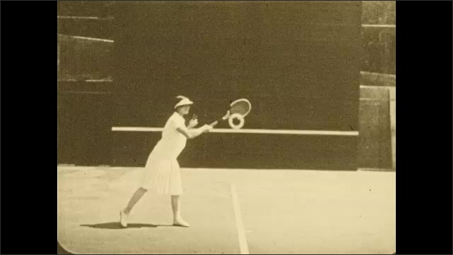 1930s: In slow motion, woman on tennis court hits ball with forehand stroke.