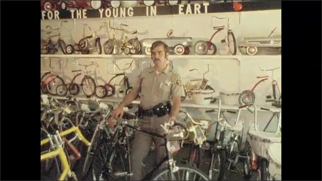 1970s: UNITED STATES: bicycle in rack in street. Police man in bike shop. Police man talks to camera.