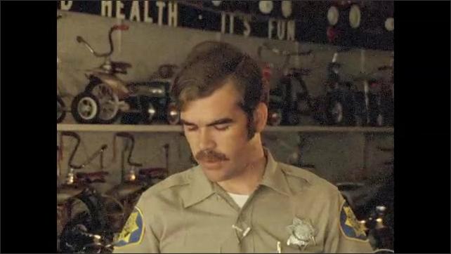 1970s: UNITED STATES: bike in bike shop. Police man talks to camera.