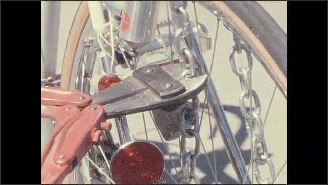 1970s: UNITED STATES: police man talks to camera. Close up of man's face. Hands use cutters to cut chain lock on bike. Close up of bell bottom trousers