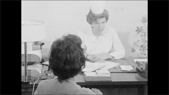 1960s: UNITED STATES: patient listens to nurse talk. Nurse takes leaflet from desk drawer.