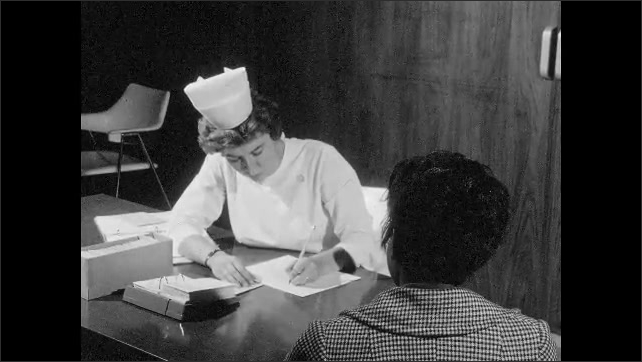 1960s: UNITED STATES: lady consults with nurse. Nurse looks at patient. Nurse asks questions to lady