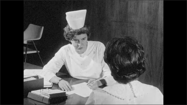 1960s: UNITED STATES: nurse makes notes about patient during meeting. Patient shakes head. Nurse talk to patient