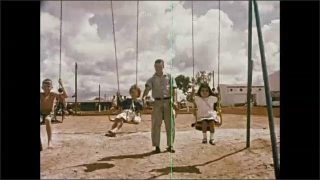 1960s: Men and women watch children spin on merry go round playground equipment. Man pushes girls on swing set.
