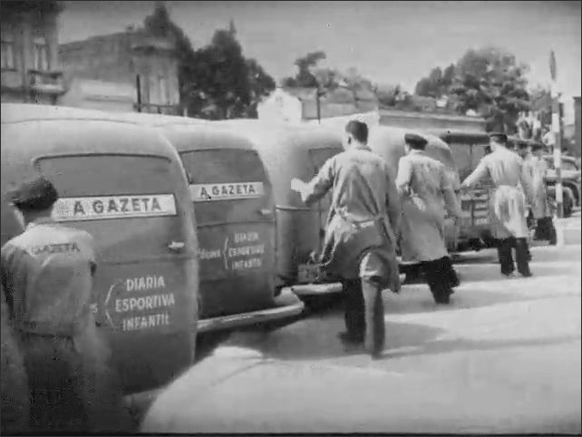 1940s: Workers fill delivery truck with bales of newspapers. Rows of A Gazeta delivery trucks are filled and doors closed. Delivery trucks pull out.