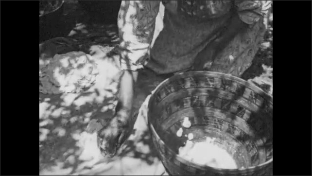 1950s: woman in native dress kneels at settling basin, scoops up piles of acorn dough, drops mixture into bowl, grabs container and stands up at outdoor cooking site. title card about hot rock oven.