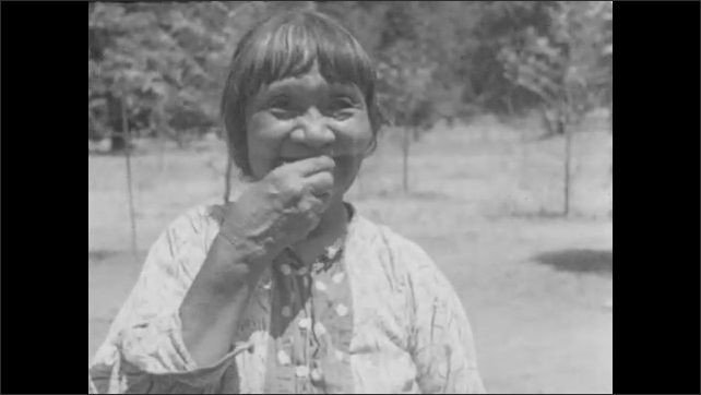 1950s: woman in native dress with bangs eats a slice of acorn bread and smiles near trees and forest.