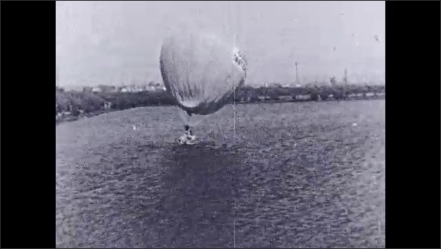 1930s: Pilot stands in front of plane, holds rabbit's foot. Intertitle card. Man holds on to large balloon, bounces on water.