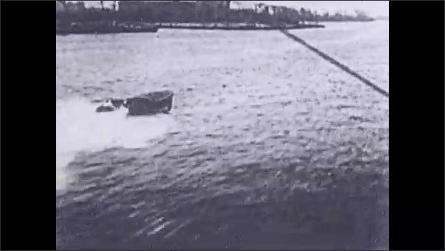 1930s: Boats speed across water. Man balances on very high pole.