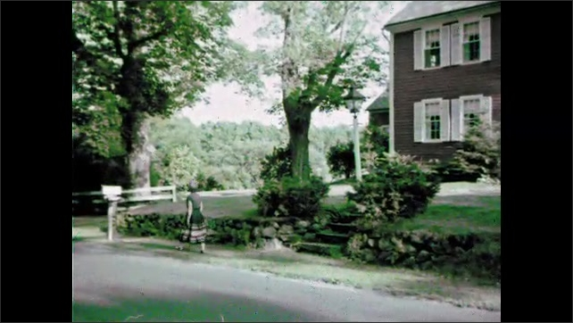 1960s: View of house. Woman exits house, walks to mailbox. Woman takes mail from mailbox.