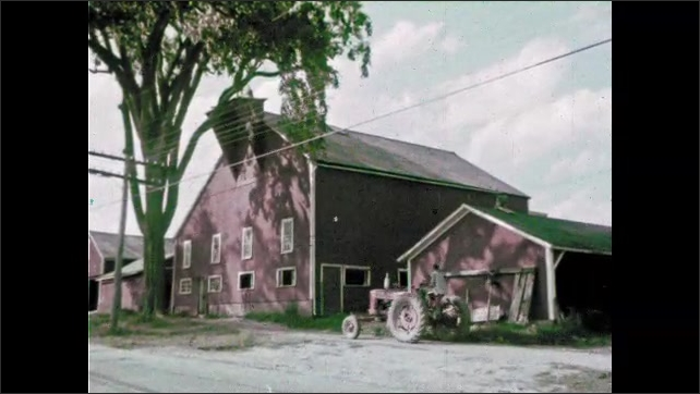 1960s: View of church. Girl rides bike past general store. Exterior of school. Tractor drives past barn. View from inside barn, cows grazing outside.