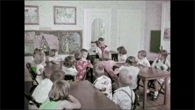1960s: Nurse watches women bandage other women, man enters, talks to woman, pan to ceiling. Kids sitting in classroom. Close up of boy. Kids at tables.