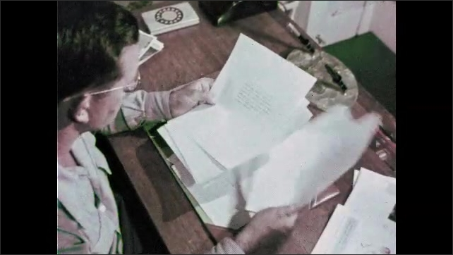 1960s: Man working at desk. High angle view, man looks at papers. Close up of text on papers.
