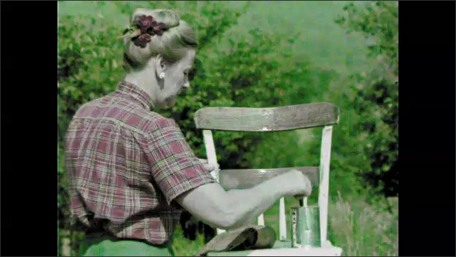 1960s: Hand scrapes finish from chair. Woman puts stain on chair.