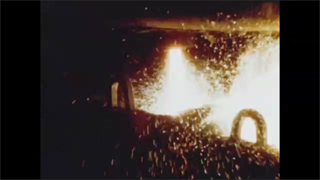 1950s: Steel mill.  Man works with molten metal.  Sparks.  Molds are removed from cast objects.