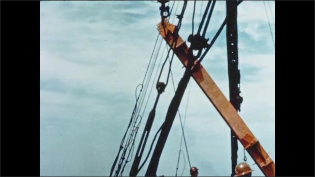 1950s: Construction workers guide steel column piece. Hook and crane lift steel girder. Workers push large bull stick across skyscraper construction area.