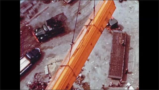 1950s: Hook and crane lift steel column. Crane lifts bundle of steel girders above trucks on site. Workman shakes steel cables.