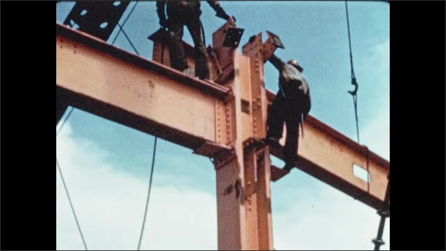 1950s: Men hand from girders and direct steel beam toward connectors.