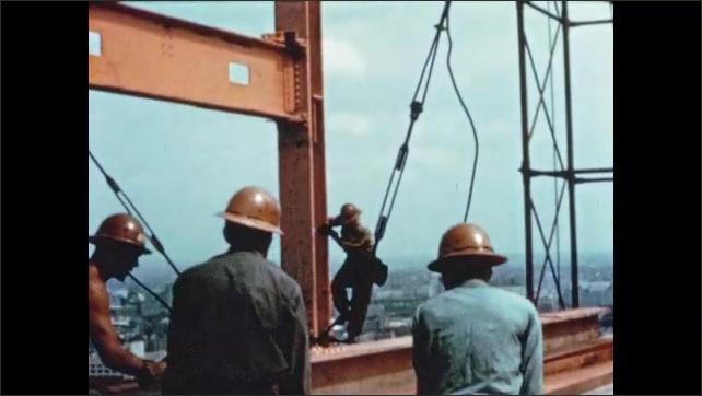 1950s: Man slides down steel beam column. Worker climbs down steel beam construction. Crane positions beam for workmen.