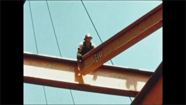 1950s: Men straddle and work on header beams. Men adjust intermediate beams onto steel construction.